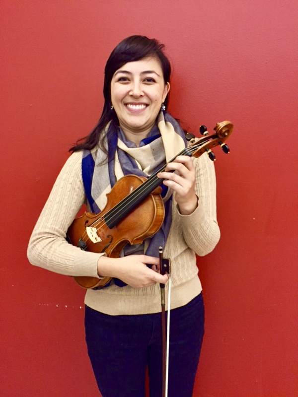 A photo of Ms. Sartori standing in front of a red wall, and smiling while holding her violin